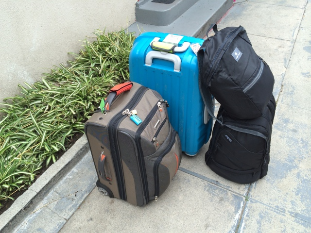 two rolling suitcases, two small backpacks