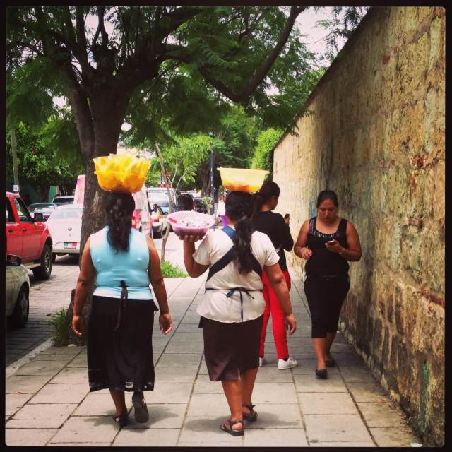2 women with mangoes on head, other women with smartphones