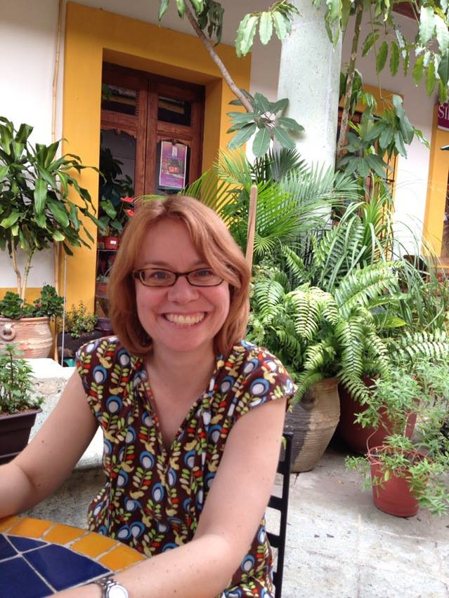 red haired woman with glasses in a beautiful courtyard