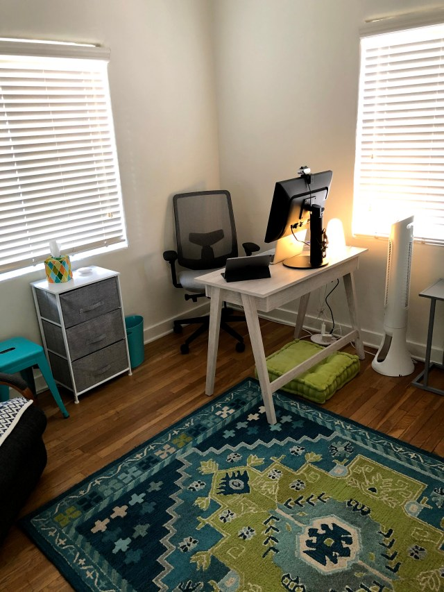 Beautiful rug, desk with computer and nice office chair.