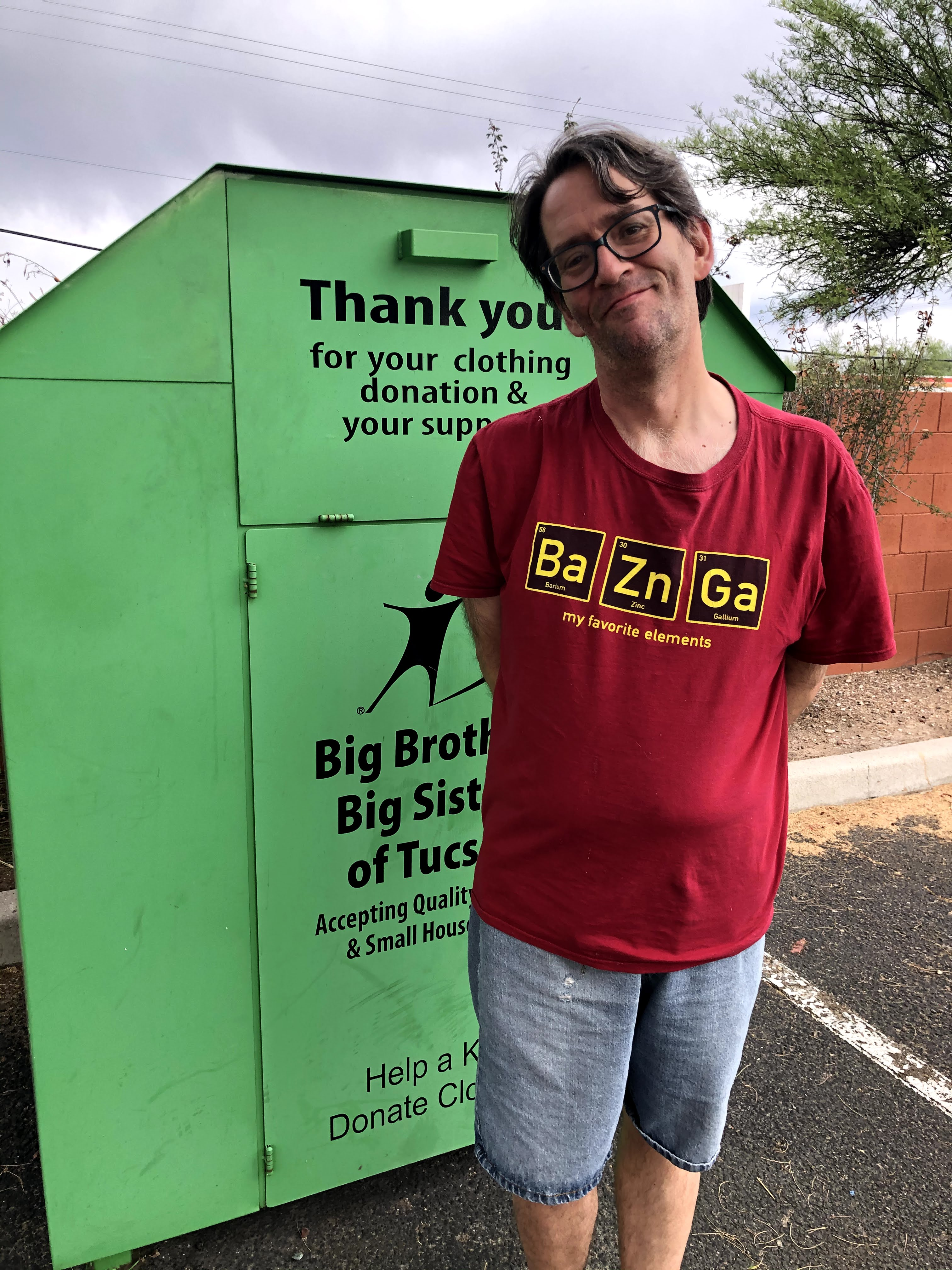 Big Brothers Big Sisters of Tucson clothing bin with James standing in front.