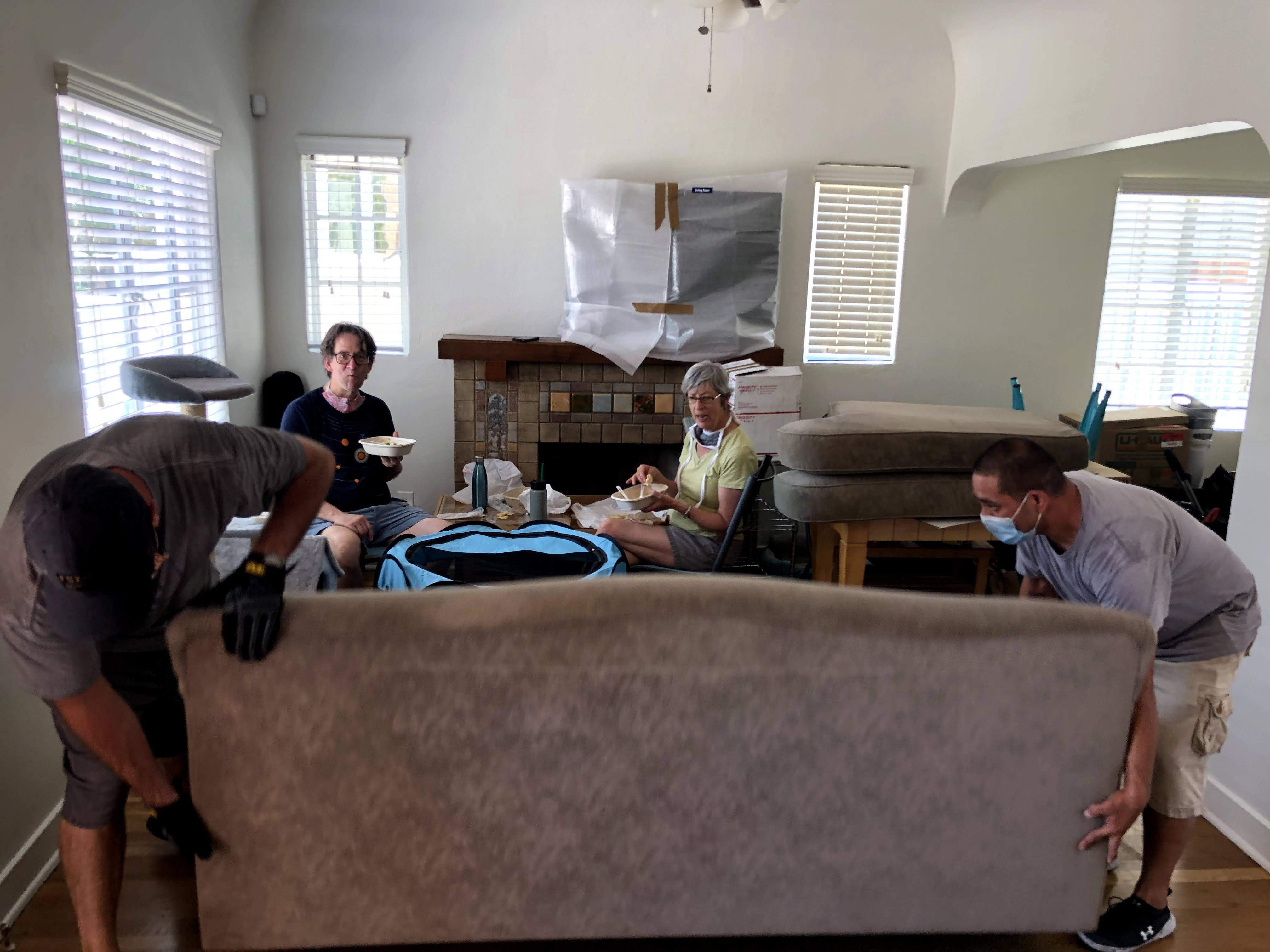 movers with masks putting couch on floor