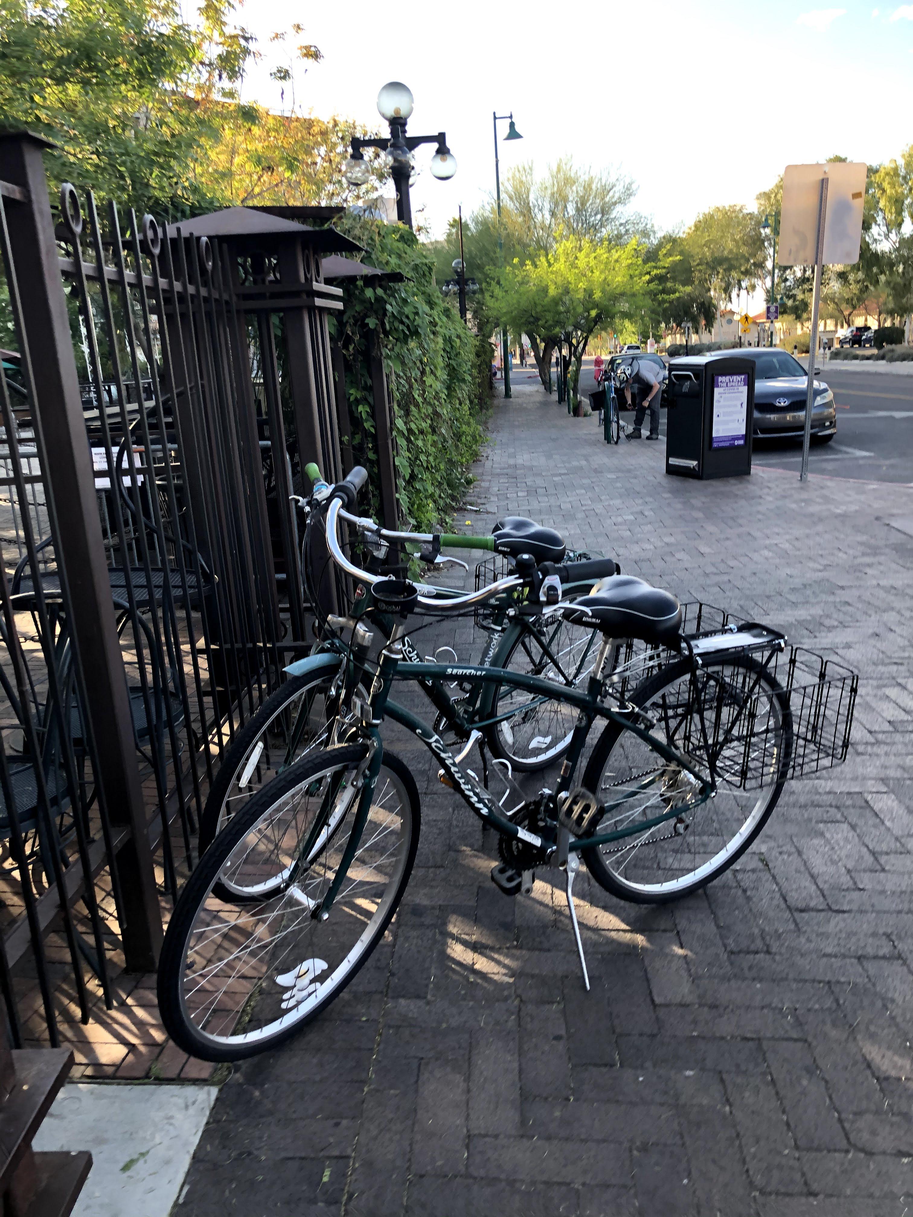 2 green bikes with baskets, near a gate