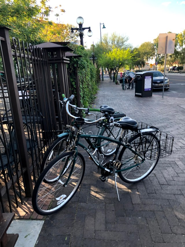 2 green bikes with baskets, near a gate
